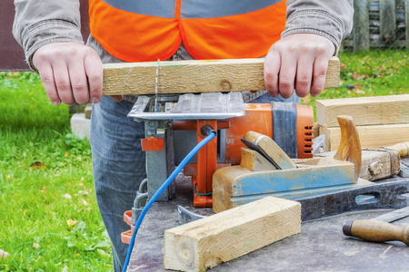 Carpenter sawing wooden plank with circular saw photo