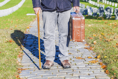 Man with cane and old suitcase in cemetery photo