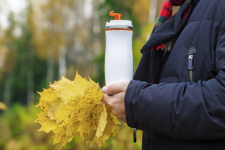 Man holding cup with drink and autumn leaves photo