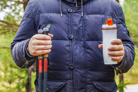 Hiker holding cup with drink and hiking poles photo