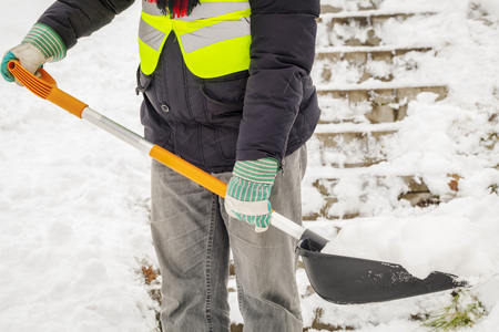 clearing the path: Man shoveling snow on stairs Stock Photo