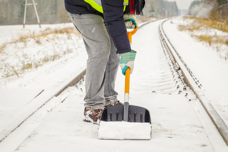 clearing the path: Railroad employee clean snow from the railway crossing