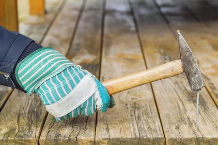 Worker hammering nail in wooden board