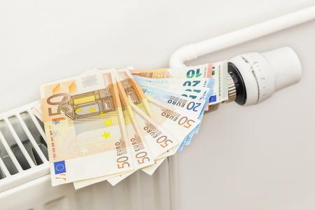 housebuilding: Euro banknotes on radiator near thermostatic valve