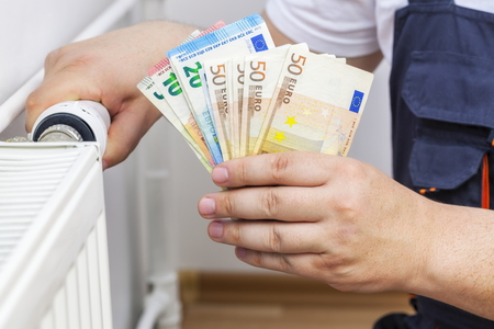 housebuilding: Man adjusting radiator and keep money Stock Photo