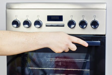 homemaker: Hand on electric cooker Stock Photo