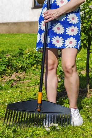 chic woman: Woman using rake in garden Stock Photo
