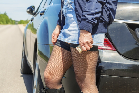 sex traffic: Prostitute with money near to the car on the road