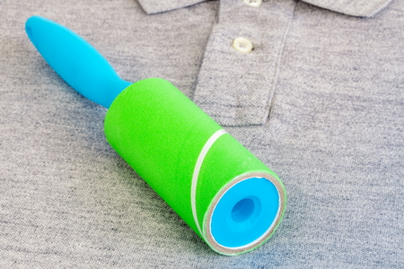 Lint roller on polo shirt close up