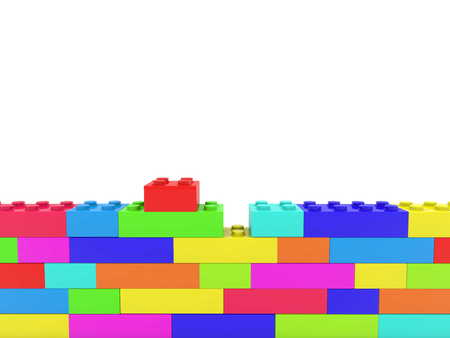 Unfinished wall of colorful toy bricks on white