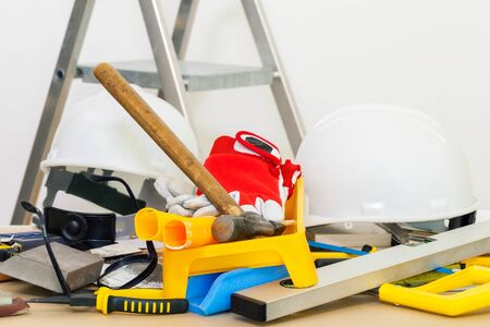 Helmet,builder tools and other construction stuff on table