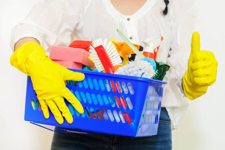 Woman cleaner holding cleaning stuff and showing thumb up