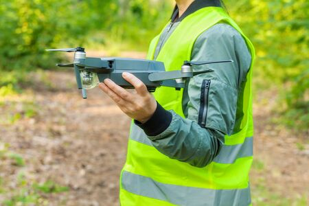 Woman holding Drone quadcopter before forest inspection 写真素材 - 128874627