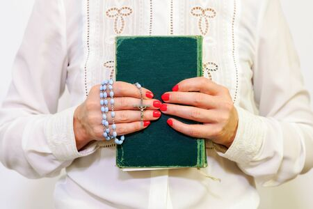 Religious woman with rosary and Holy Bible