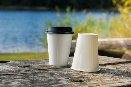 Two take away coffee cups on bench