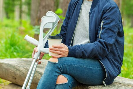 Disabled female with crutches drinking coffee in the park on bench