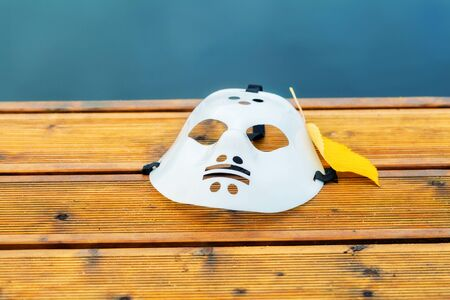 Halloween hockey mask on pier near water