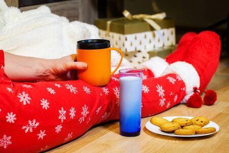Woman in Christmas Pajama holding cup of coffee in hand at legs with knitted socks near Christmas Imagens