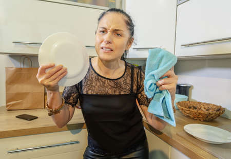 Angry woman smashing plate in kitchen