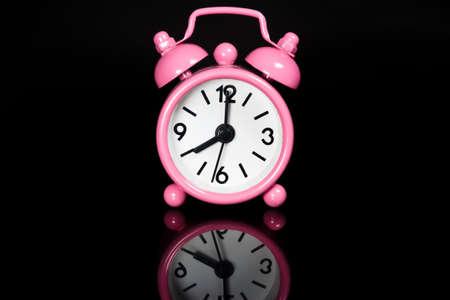 Pink Alarm Clock On Black Background photo