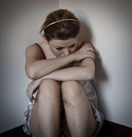 mujeres tristes: Las mujeres tristes sentados en un rinc�n oscuro con un golpe en la pierna