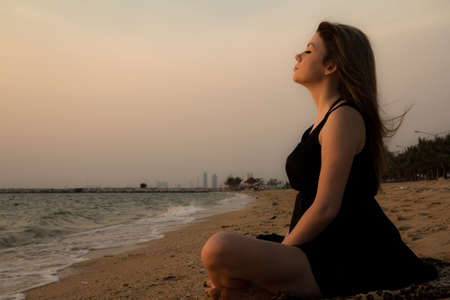 woman training yoga on the beach at sunset photo