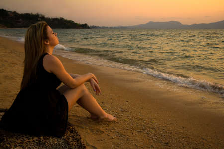 woman sitting and relaxing on the beach at sunset Stock Photo