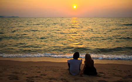A Couple interracial lover sitting together on the beach at sunset