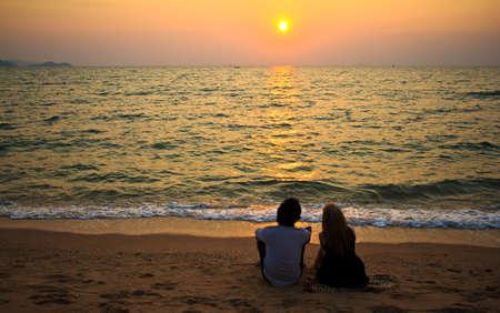 romantico: Un amante de la pareja interracial sentados juntos en la playa al atardecer