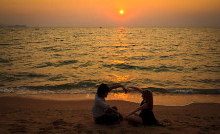 Interracial Couple loving on the beach watching sunset photo