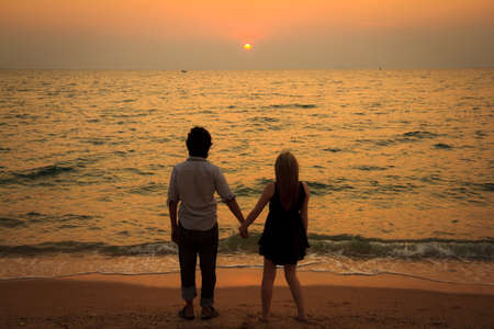 A interracial lover holding hands together on the beach at sunset photo
