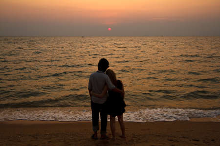 A Interracial lover Couple huging on the beach watching sunset photo