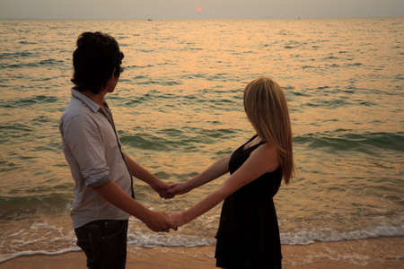 Interracial lover Couple holding hands together on the beach at sunset photo