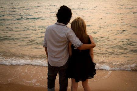 interracial marriage: Coppia amante interrazziale huging sulla spiaggia guardando il tramonto Archivio Fotografico