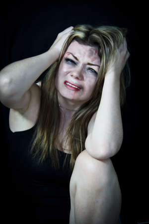 Scared white woman pretending holding her head in pain with a black background photo