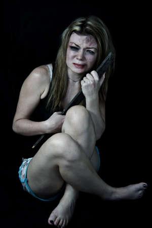 mujer golpeada: Mujer asustada y golpeada simulando la celebración de un trozo de madera para protegerse de sus atacantes