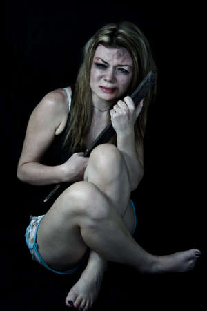 Scared and beaten woman pretending holding a piece of wood to protect herself from her attackers photo