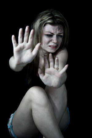 beaten woman: STOP Violence women, Scared and beaten white woman pretending holding out her hands in the  STOP  position