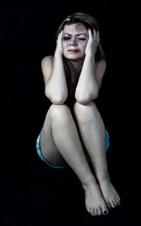 mujer golpeada: Asustada mujer golpeada blanco simulando la celebración de su cabeza en el dolor con un fondo negro