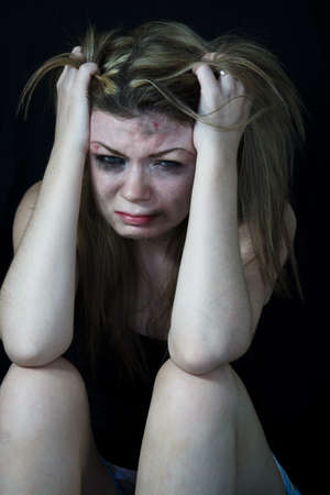 Scared and beaten white woman pretending sitting in pain and crying and  pulling her hair photo