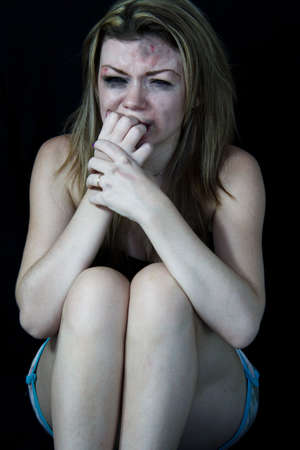 miserable: Scared and beaten woman pretending crying with a black backgound Stock Photo