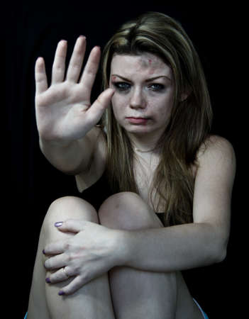 STOP Violence women, Scared and beaten white woman pretending holding out her hand in the  STOP  position Stock Photo