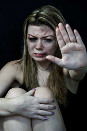 STOP Violence women, Scared and beaten white woman pretending sitting in pain holding forward her hand in a  STOP  position photo
