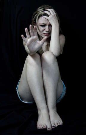 mujer golpeada: Impedir que las mujeres la violencia, la mujer asustada y golpeada blanco simulando sesión en el dolor que sostienen hacia adelante su mano en una posición de parada con un fondo negro