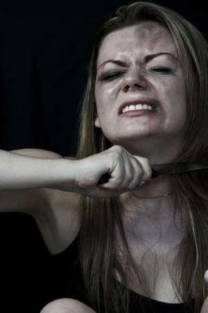 mujer golpeada: Mujer golpeada blanco simulando la celebraci�n de un cuchillo en la garganta con un fondo negro