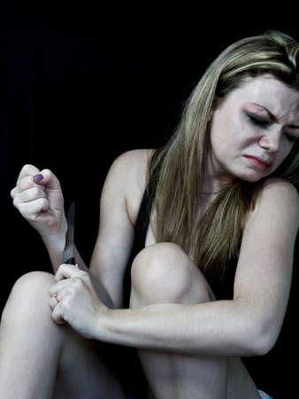mujer golpeada: Mujer golpeada blanco simulando corte en la mu�eca sobre un fondo negro Foto de archivo