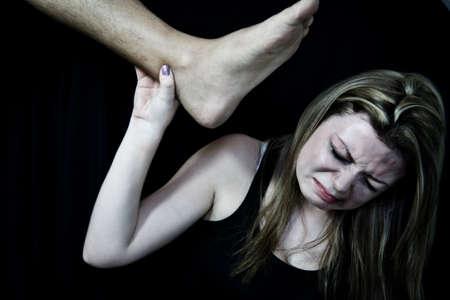 mujer golpeada: Impedir que las mujeres Violencia, mujer golpeada blanco fingiendo ser pateado en la cabeza sobre un fondo negro