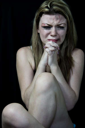 Scared and beaten white woman pretending crying and begging on a black background Stock Photo