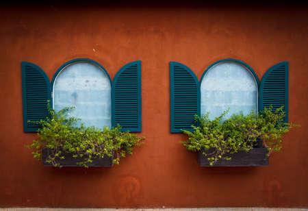 open window: Open Window With Flower Basket On Orange Wall Stock Photo