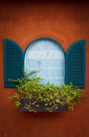 Open Window With Flower Basket On Orange Wall photo
